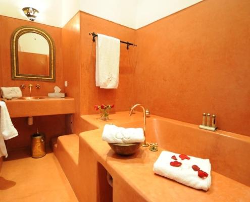 Bagno con vasca, lavandino e pavimento in tadelakt rosso