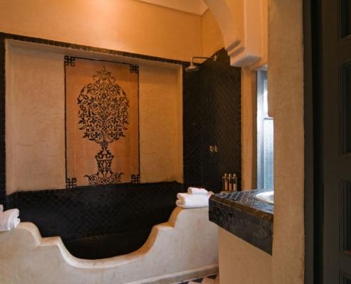 Vasca da bagno in tadelakt e piastrelle nere